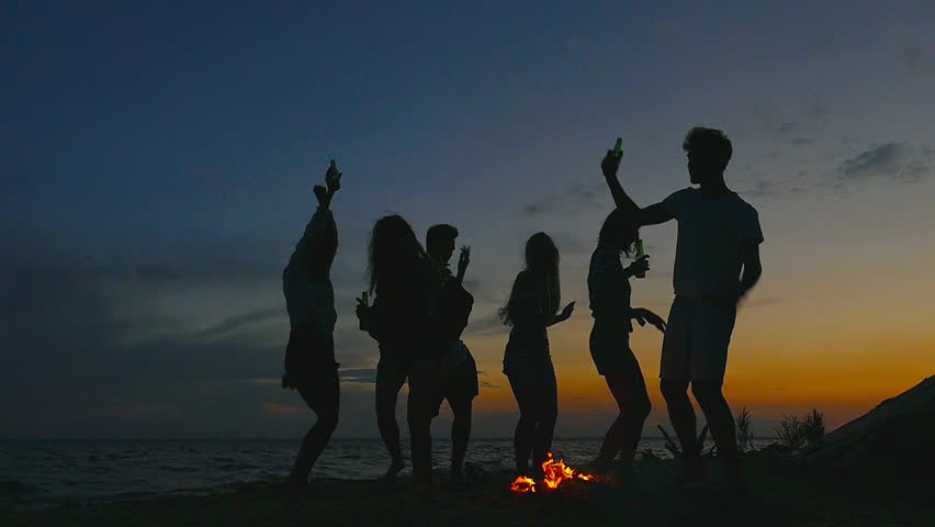Group of people at the beach near the bonfire. Slow motion. | Shutterstock HD Video #1017100678