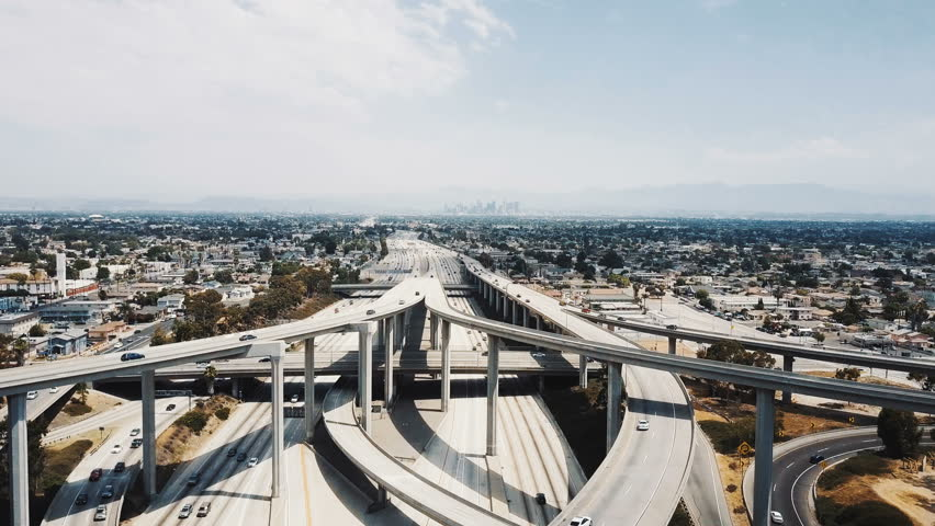 Drone flying forward over epic multiple level highway intersection in Los Angeles, traffic moving in all directions. | Shutterstock HD Video #1017108598