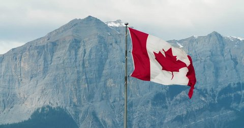 Canadian Flag Blowing in the Wind with Rocky Mountains in the Background, West Coast, Banff, Canmore, Alberta, Canada