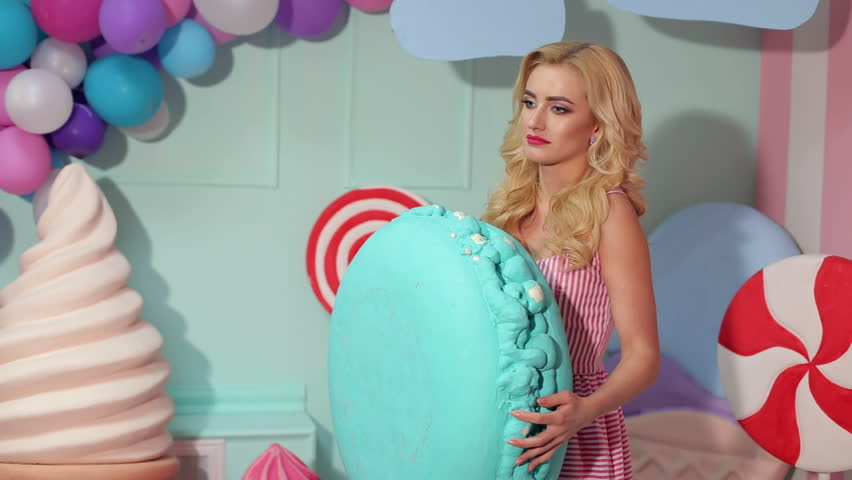 A slender beautiful girl in a pink striped dress poses in the Studio with a big marshmallow in her hands. Happy girl with a big marshmallow on a background of balloons and a huge candy on stick