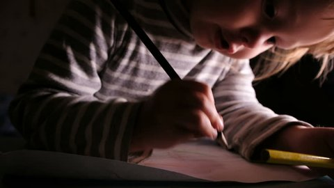 Baby girl learns to draw with pencils on paper, slow motion