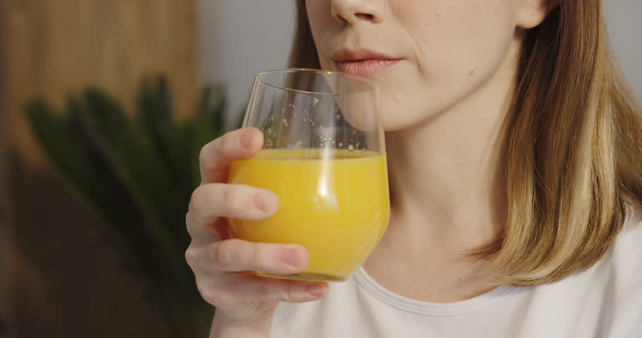 Close up of the young Caucasian pretty woman drinking orange juice from a glass and smiling to the camera.
