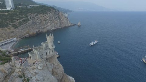 Shooting from the air of architectural landmark castle Swallows nest in Gaspra, Yalta region, Crimea. Tourists walking on the pier to get on a ship for sea excursion. Beautiful coast with beach, trees