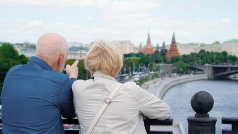 Back view of happy senior couple standing on observation deck looking around city. Pensioners traveling in Russia viewing attractions. Moscow city landscape and river on background. Hand-held camera