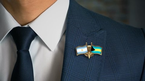 Businessman Walking Towards Camera With Friend Country Flags Pin Argentina - Bahamas