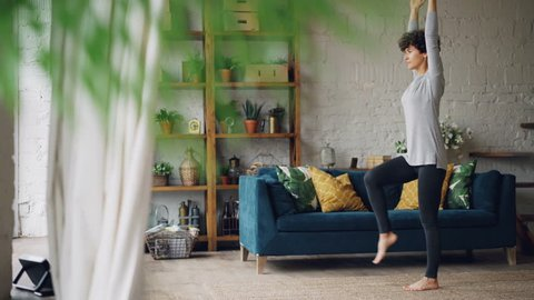 Active person is doing yoga at home practising balance exercises on one leg standing on floor alone. Beautiful loft style flat with furniture and plants is visible.