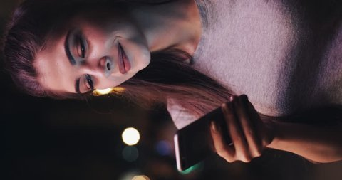 Vertical video. Young attractive woman using mobile phone on street of night town. Woman using mobile phone for business communication voice message.