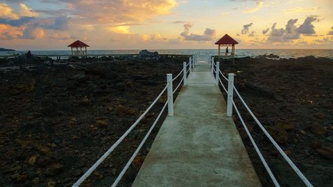 Timelapse of colourful sunrise at Tanjung Balau jetty. New walking path been build to ease tourist enjoy the scenery. Tanjung Balau is fishing hub at Johor, Malaysia. camera pan right