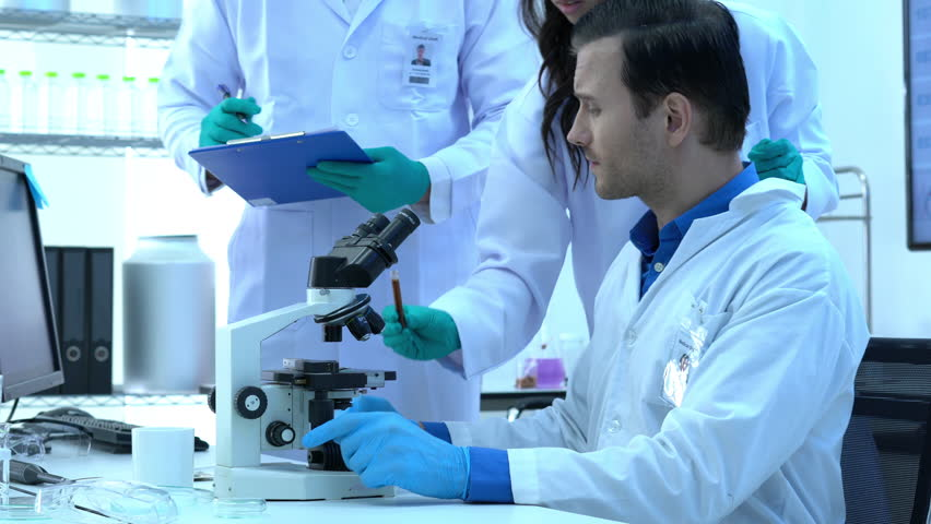 Scientist is looking through microscope with colleagues working in modern laboratory or medical center together. Concept of science, testing development and lab industry. #1017238738