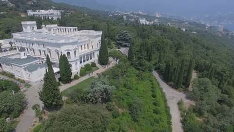 Shooting from the air of Livadiysky Palace, Yalta region. Tourists walking  cross the beautiful park of great conifers trees, posing, making photos. Aerial video of  South coast of Crimea.