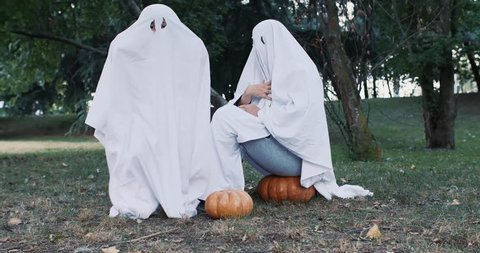 father and son playing ghosts with white sheets in the garden