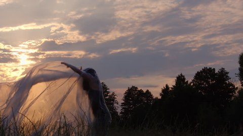 Slow Motion Shot Of A Woman Thrashing The Plastic Foil Surrounding Her And Falling Down To Earth In A Meadow At Sunset