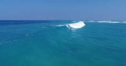 Slow motion aerial footage a stand up paddler riding a big wave with lots of other big waves in the background in Kailua Kona, Hawaii.