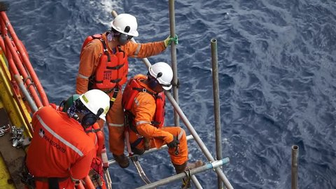 KELANTAN, MALAYSIA - September 28 2018 : Unidentified offshore workers with fall arrestor and floating device working overboard for scaffolding activities at the edge of oil and gas platform.