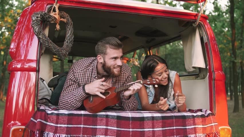 Happy young mixed race couple playing instruments and having some fun in retro hippie minibus in forest, slow motion