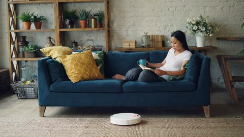 cc8e3a7294 Beautiful Asian girl is reading book resting on sofa in living room while  robotic vacuum cleaner