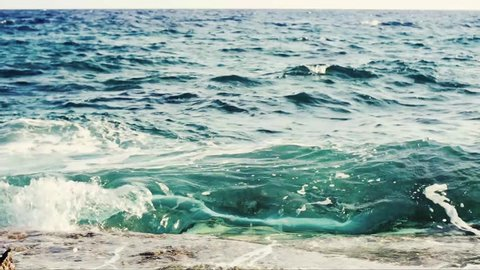 Sea waves hit the rocky shore scattering into small particles
