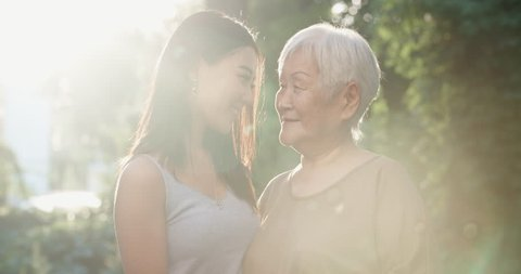 Happy asian grandmother and her teen granddaughter standing in park, hugging each other and smiling - portrait shot 4k