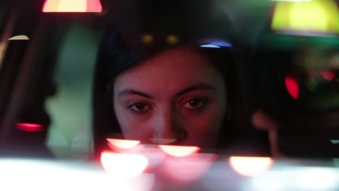 Woman driving at night seen through rear-view mirror