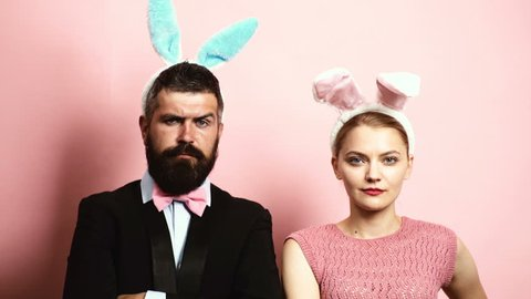 Bearded man and blond woman raising eyebrows on a pink background with ears on their heads. Concept of fashionable hare. Man and woman with hare ears on a pink background