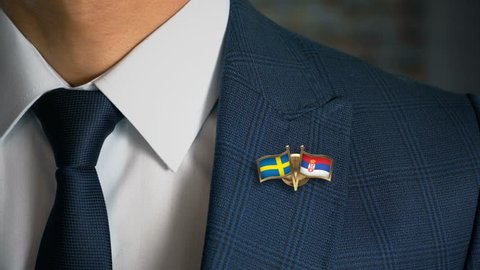 Businessman Walking Towards Camera With Friend Country Flags Pin Sweden - Serbia