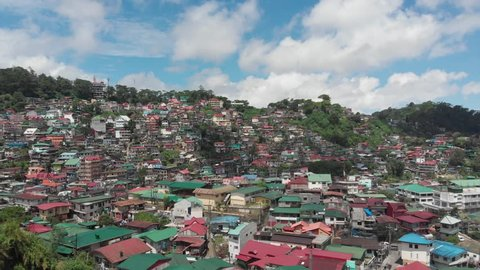 An overlooking drone shot of Baguio City, with a lot of houses on a Mountainous Region.