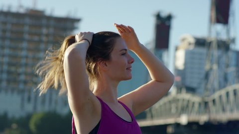 Athlete Pulls Her Hair Up Into Ponytail, Getting Ready For Workout, Cityscape Behind Her
