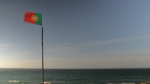 Portuguese flag waving next to sea on a summer day with copy space