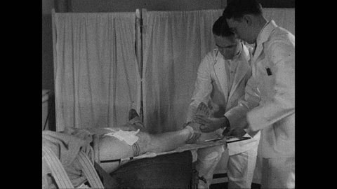 1930s: UNITED STATES: doctor bandages patient's leg in splint. Patient with leg in splint