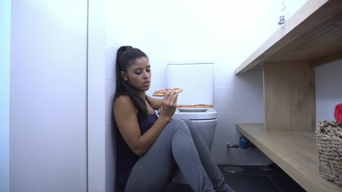 Attractive young and sad bulimic young woman feeling guilty and sick eating  while sitting on the floor next to the toilet in eating disorders anorexia  and bulimia concept