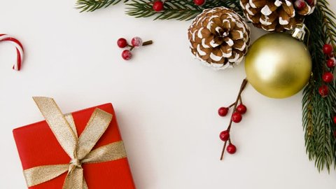 christmas, holidays and festive concept - gift packed into red wrapping paper and decorations on white background
