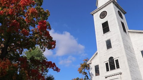 Time lapse of clouds over an old white church in new England in the fall season, old colonial clock tower church in New England, Salem witch trials in Massachusetts.