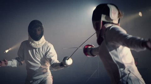 Footage of two fencing athletes duel . Two Professional Fencers Show Masterful Swordsmanship in their Foil Fight. Fencing training . Shot on ARRI ALEXA camera .