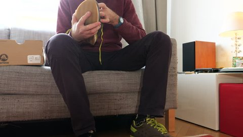 PARIS, FRANCE - CIRCA 2018: Young man testing measuring after unboxing new fashion running shoes from Crocs shoes lacing on sofa before getting out