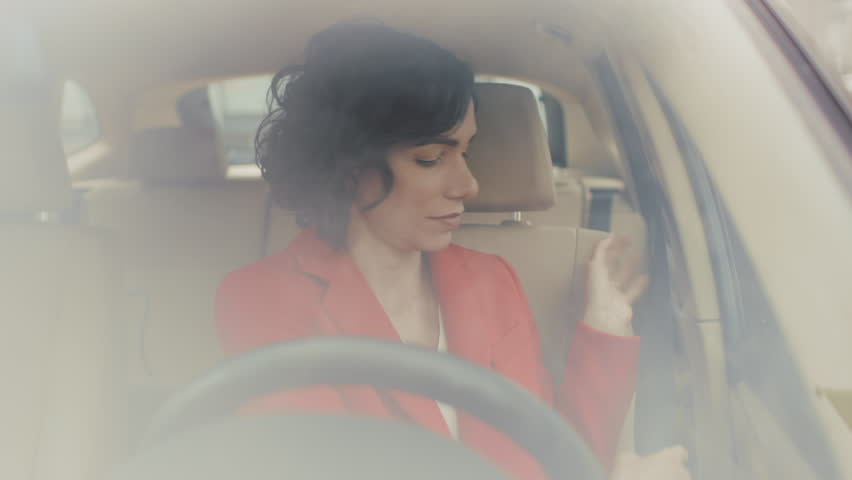 Beautiful Young Woman Gets into the Car, Fastens the Seatbelt, Starts Engine and Begins Driving. Camera Shot Made from the Front Windshield.