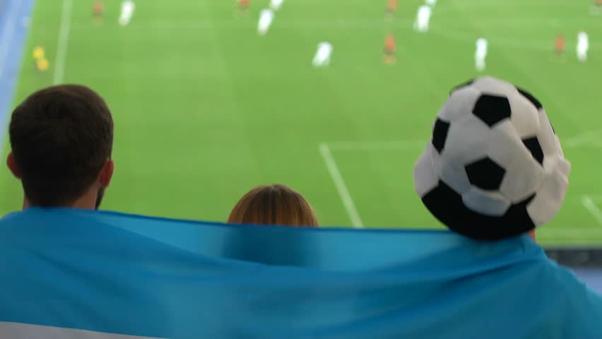 Fans wrapped in Argentinian flag jumping and watching football at stadium | Shutterstock HD Video #1017801538