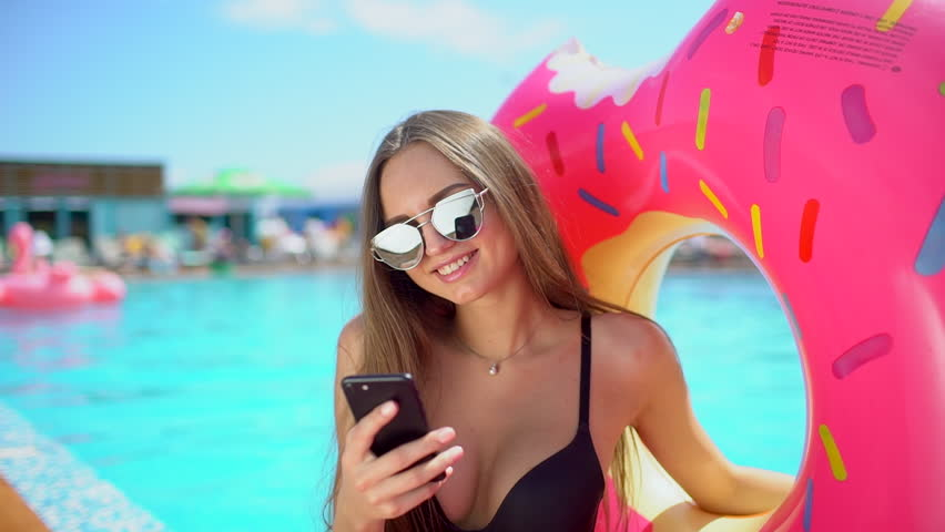 Beautiful young bikini woman in pool on beach with smartphone. Bikini girl in pool using, texting on mobile phone. traveler woman smiling tourism happy holiday beauty vacation summertime summer time