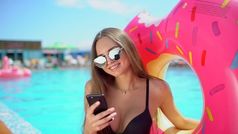 Beautiful young bikini woman in pool on beach with smartphone. Bikini girl in pool using, texting on mobile phone. traveler woman smiling tourism happy holiday beauty vacation inflatable summer time