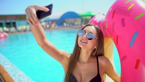 Beautiful young woman in summer taking selfies on smartphone. bikini girl making picture photos on beach Summer, girl take selfie at pool. concept of  tourism vacation beauty hotel tour happy holiday
