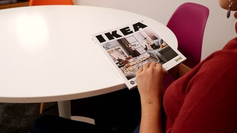 BOLOGNA, ITALY - OCTOBER, 2018: Young woman reading IKEA Catalogue before buying furniture for her new house. Ikea is a Swedish multinational group that designs and sells ready-to-assemble furniture.