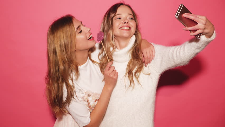 Two beautiful carefree girls taking selfie with a smart phone. Women make funny faces. Positive models posing over pink background with paper lips on stick. Female ready for party. 4k | Shutterstock HD Video #1017888118