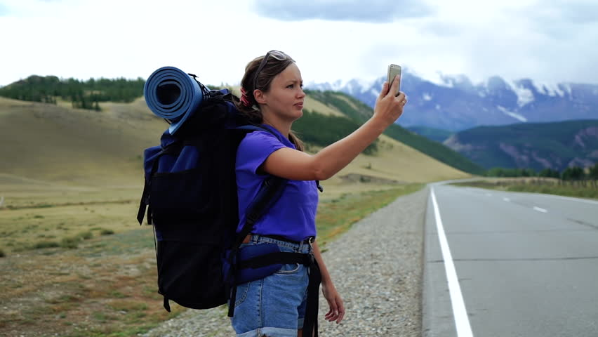Young tourist woman with a backpack and sunglasses is trying to catch the phone signal on a mountain road. There are snow mountains in the background | Shutterstock HD Video #1017908938