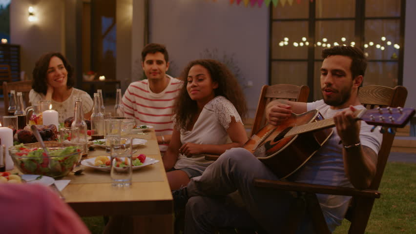 Sitting at the Dinner Table Handsome Young Man Plays the Guitar For a Friends. Group of Young People Listening to Music at the Summer Evening Garden Party Celebration. | Shutterstock HD Video #1018016158
