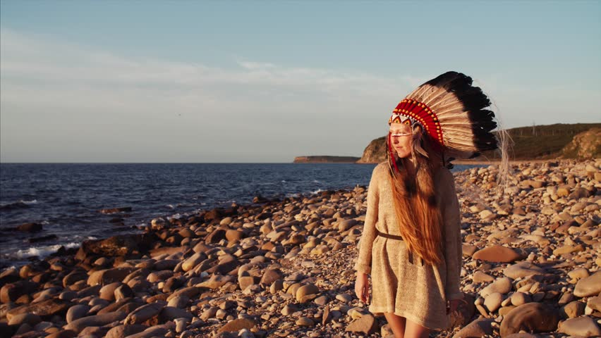 Beautiful redheaded woman with long hair and bright make up in native american indian headdress is walking along the beach looking into the camera. Great sunrise | Shutterstock HD Video #1018036798
