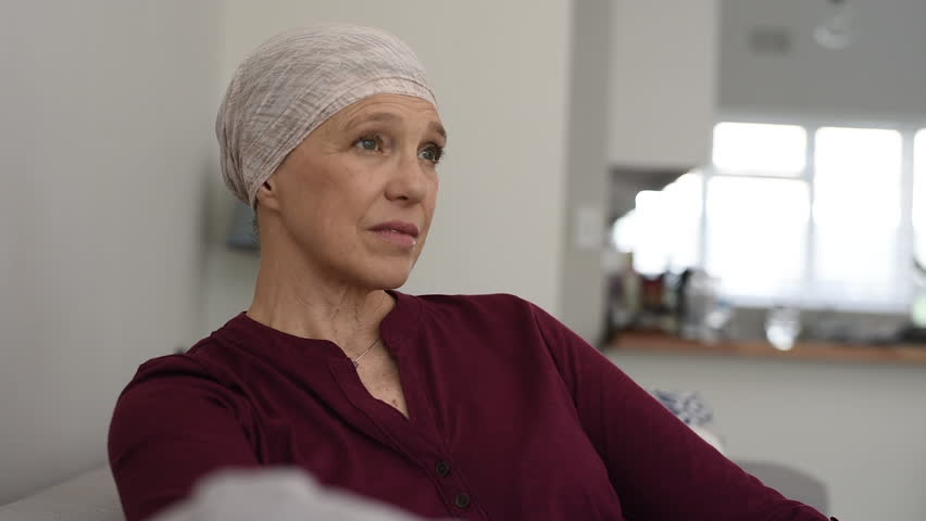 Portrait of mature woman recovering after chemotherapy and looking at  camera. Senior woman fighting breast cancer and wearing a headscarf.