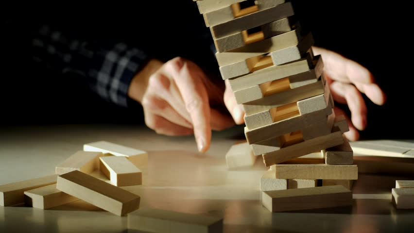 Business risks in the business. Jenga falls on the table, the tower falls. Slow motion video. Male hand pulls out a wooden brick and construction collapses | Shutterstock HD Video #1018100848