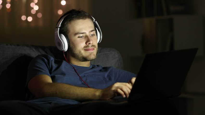 Happy man watching videos in a laptop sitting on a couch in the living room in the night at home #1018131268