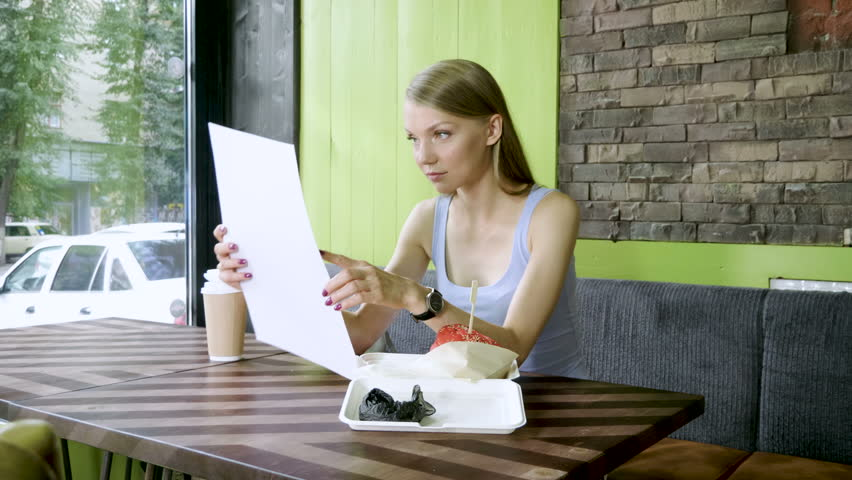 The young woman looking at restaurant menu, going to eat a hamburger and drink coffee. 4K