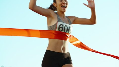 Female athlete on track. Young asian runner runing on track of stadium, happily crossing the red finish line, getting ready for competition