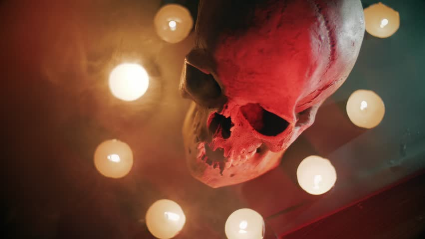 The skull in the circle of candles, on a foggy background, Halloween theme.    Shutterstock HD Video #1018155928